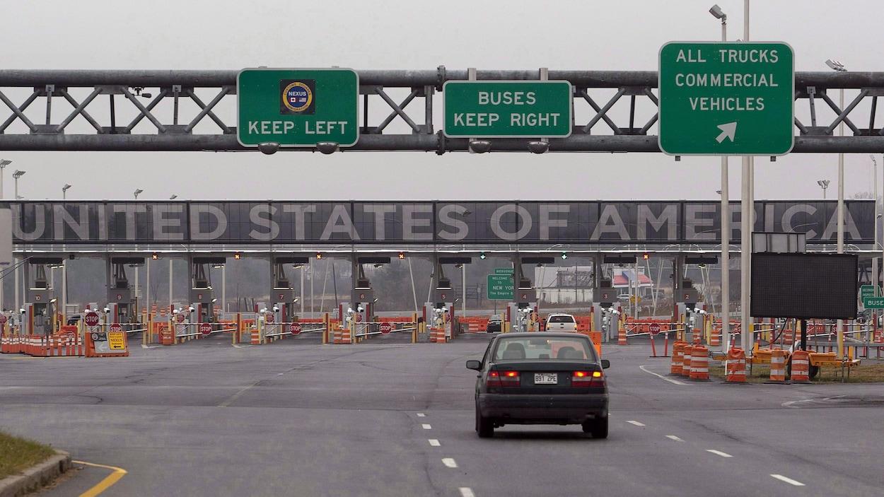 Une voiture s'approche d'un gros poste douanier. On voit l'indication ''United States of America'' en gros au-dessus les pancartes.