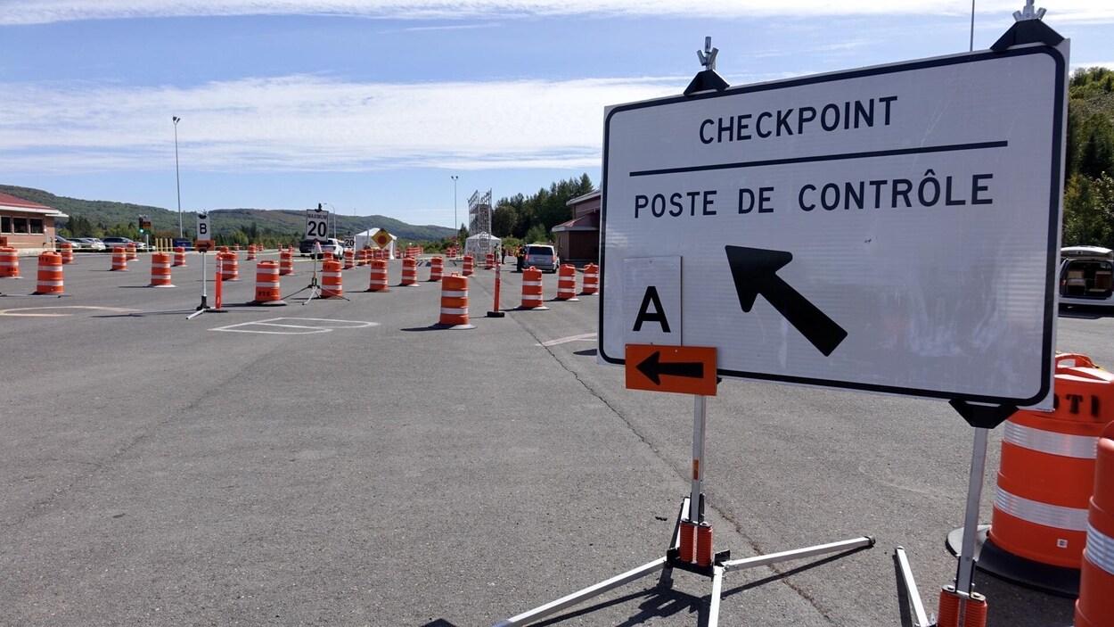 Une affiche indique là où se diriger avec son véhicule au poste de contrôle.