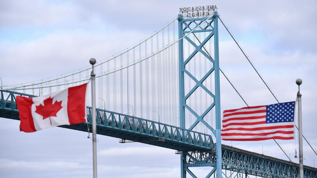 Les drapeaux canadien et américain qui flottent devant le pont Ambassador.
