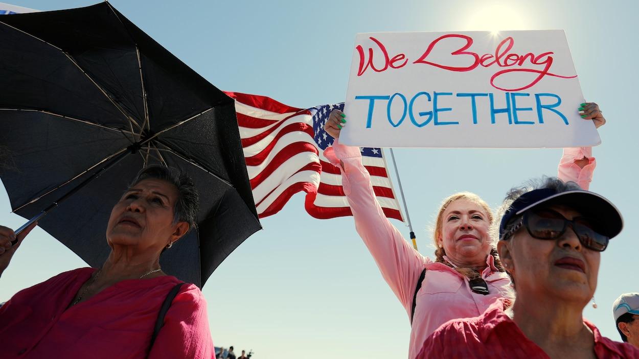 Une femme tient une affiche avec le message « Nous appartenons tous à la même communauté » en marge d'une rencontre entre des maires d'un peu partout aux États-Unis, jeudi, près d'un centre de détention d'enfants migrants à Tornillo au Texas.