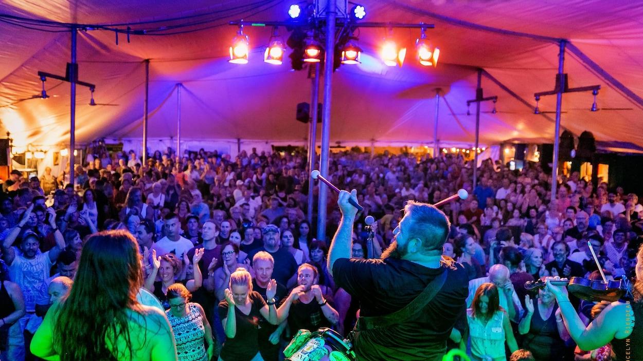 Un chapiteau plein lors du 22e Festival des traditions du monde de Sherbrooke alors qu'un groupe joue sur la scène.
