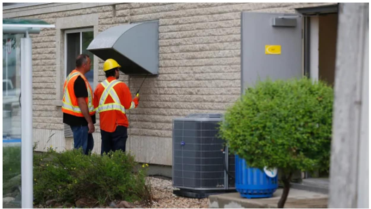 Deux travailleurs du secteur du gaz vérifient la qualité de l'air aux bouches de ventilation.