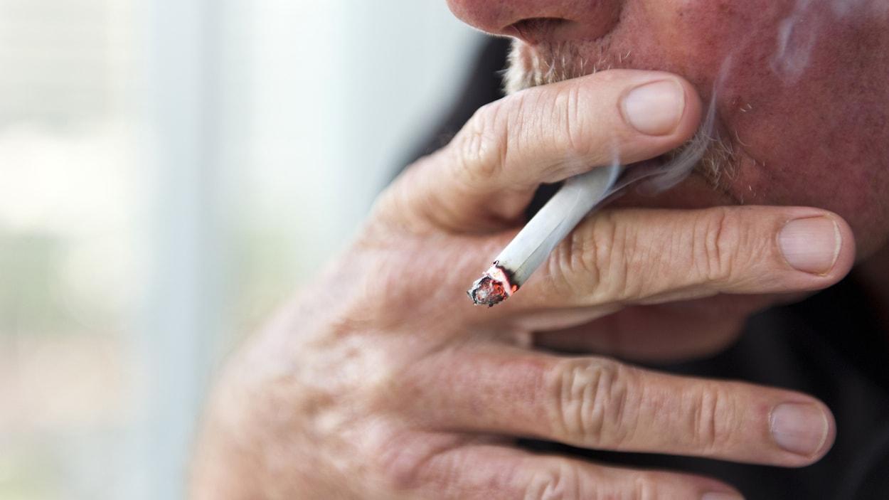 Un homme fume une cigarette.