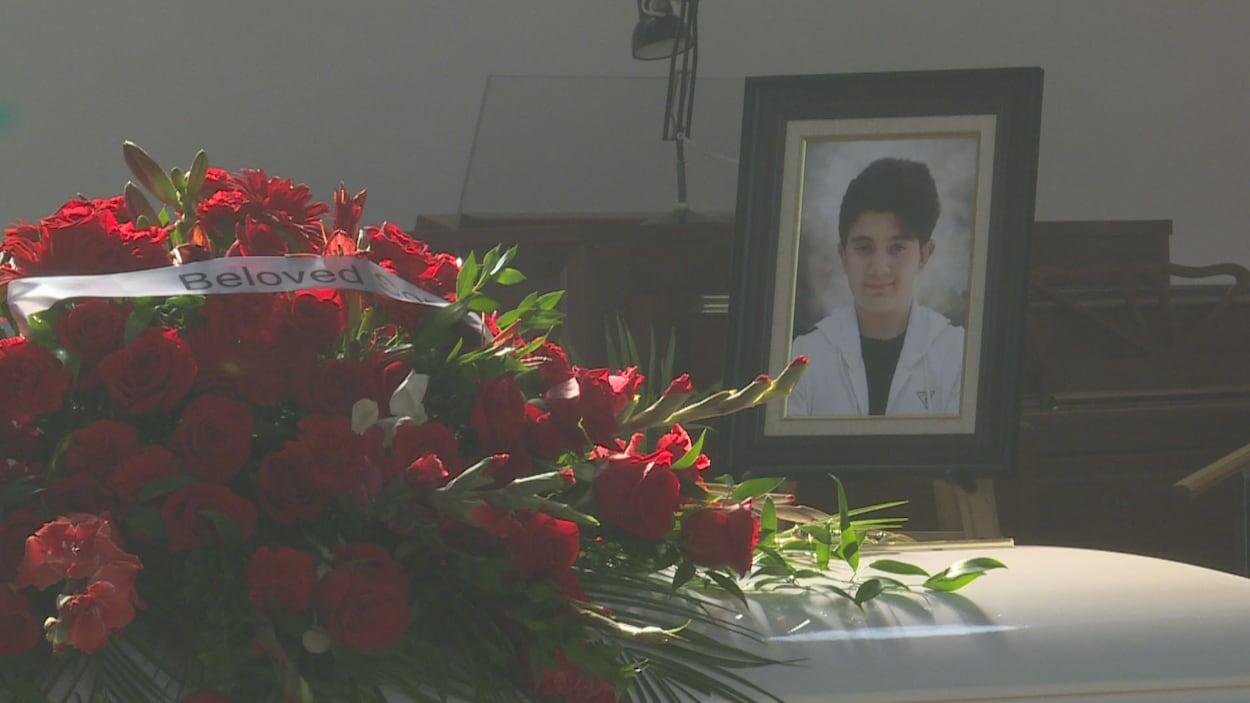 Un cercueil sur lequel sont posées des roses et à côté duquel se trouve un cadre avec la photo de Simon Khouri.