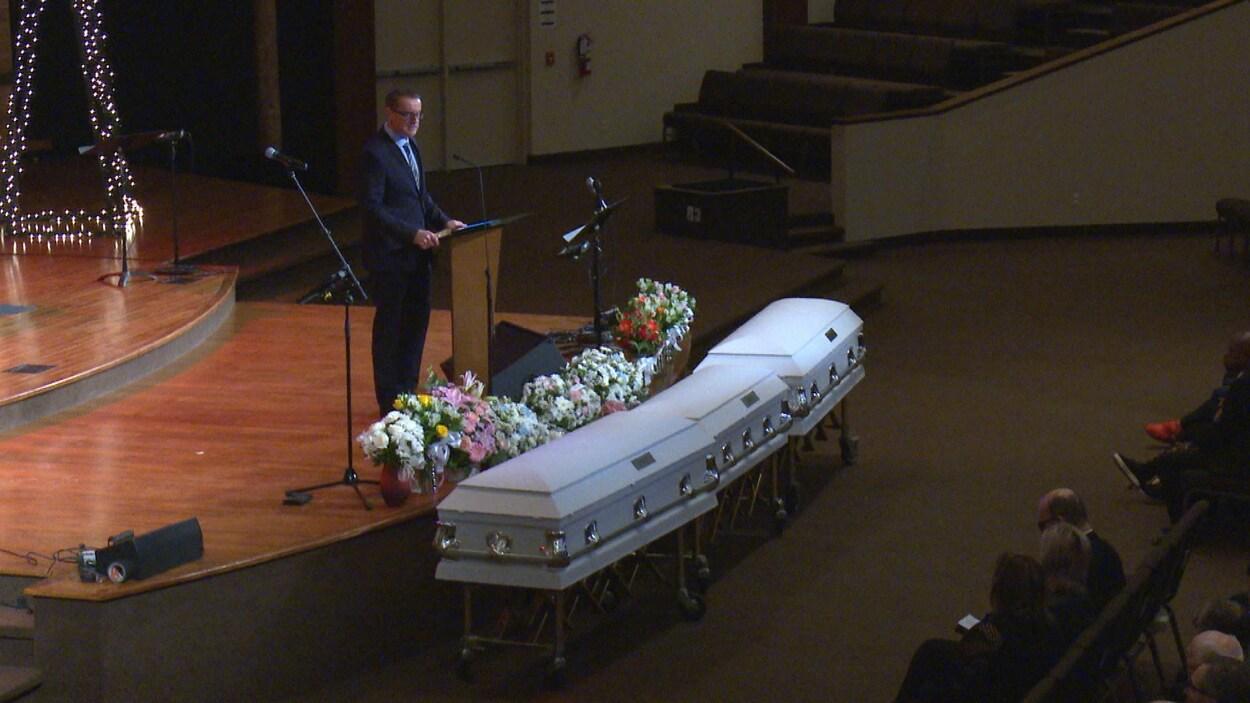 Trois cercueils blancs dans une salle lors de funérailles.