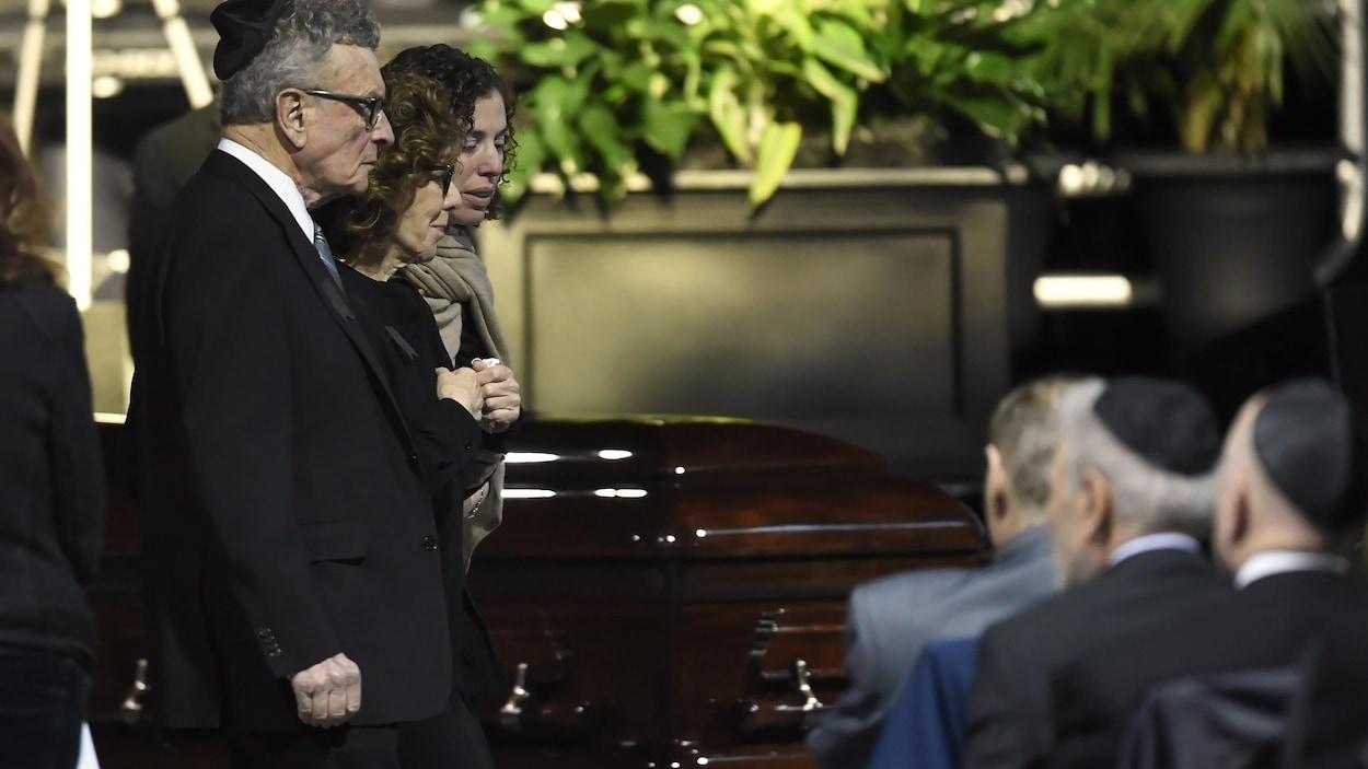 Deux femmes et un homme vêtus de noir près de l'un des deux cercueils.