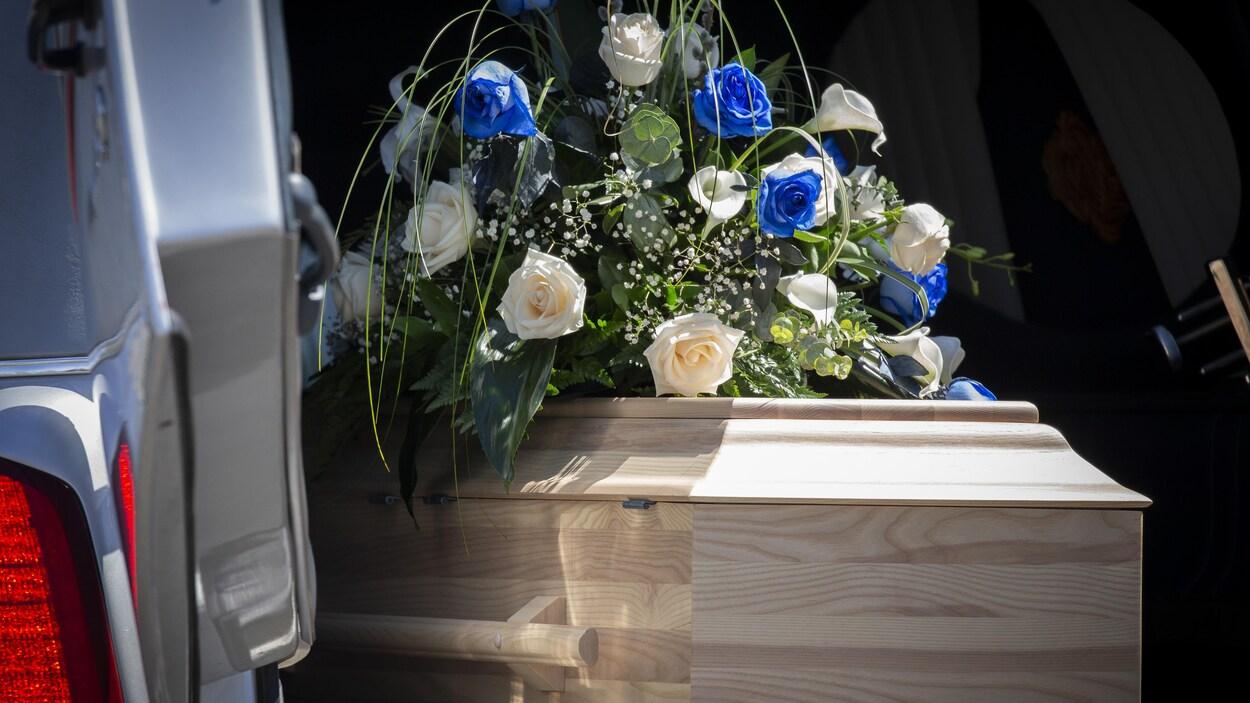Le cercueil de la petite fille avec une gerbe de fleurs sur le dessus.