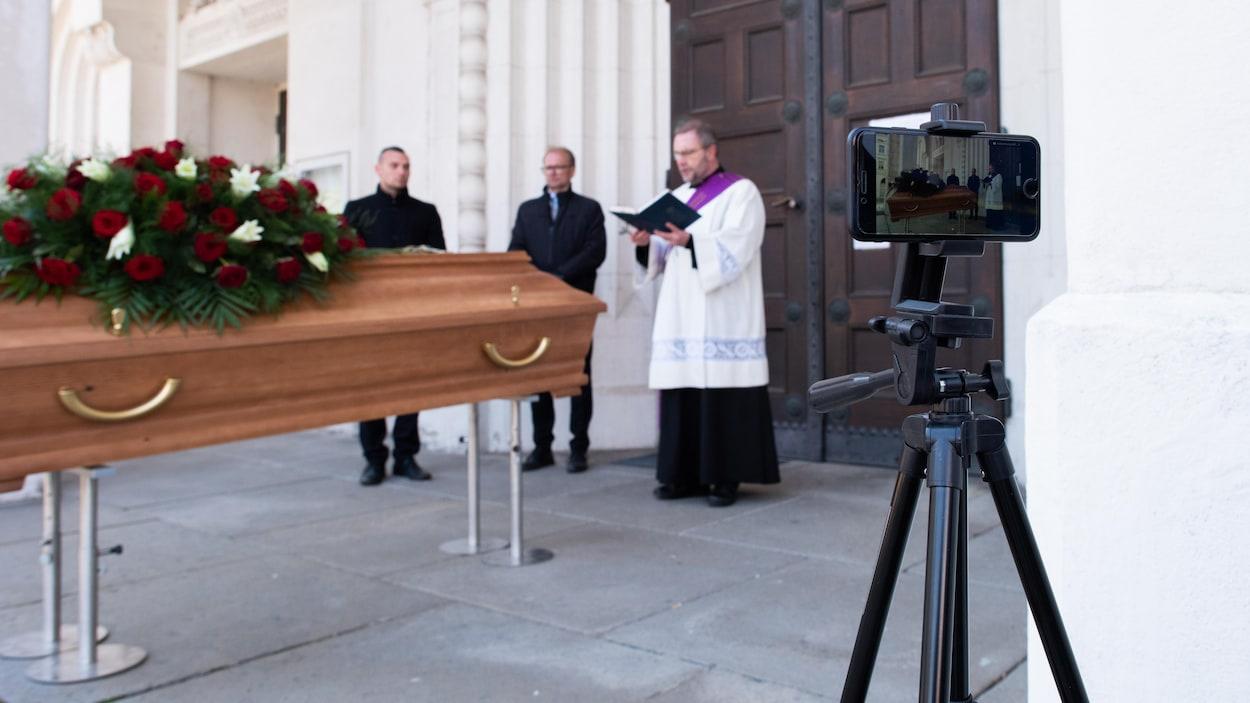 Un prêtre parle devant un cercueil en étant filmé par un téléphone cellulaire sur trépied.