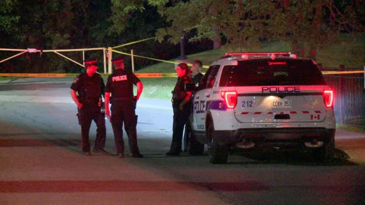Photo de quatre policiers près d'un véhicule de police, le soir.