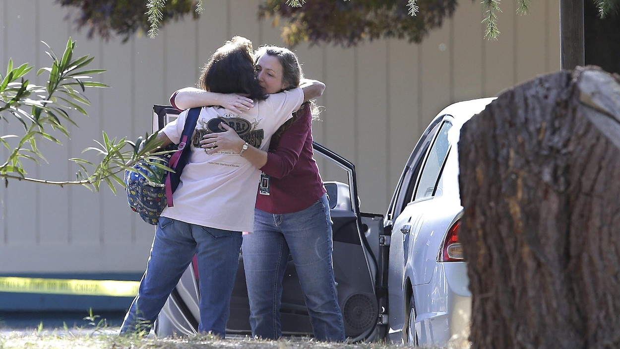 Deux femmes se serrent dans leurs bras à l'extérieur de l'école élémentaire de Rancho Tehama, où un tireur a ouvert le feu le 14 novembre 2017.