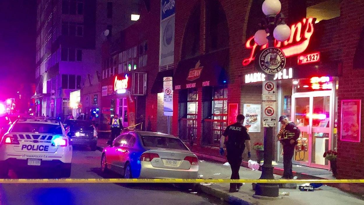 Des véhicules d'urgence sont à l'intérieur d'un périmètre de sécurité, à l'intérieur duquel se trouvent deux policiers devant un restaurant.