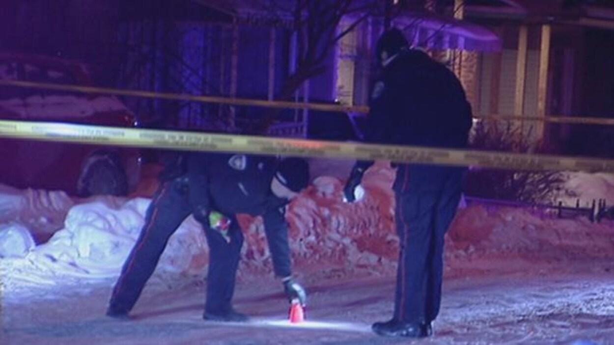 Deux policiers enquêtent dans le périmètre de sécurité.