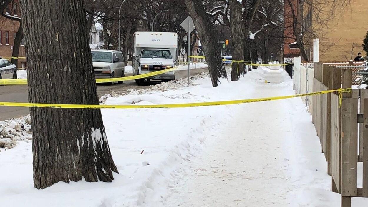 Du ruban jaune de la police entoure un terrain sur une rue enneigée.