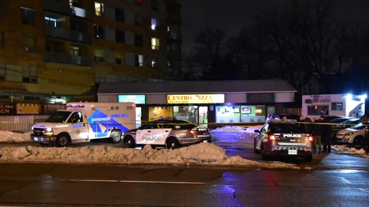 Des voitures de police et une voiture d'ambulanciers devant des commerces dans une rue la nuit.