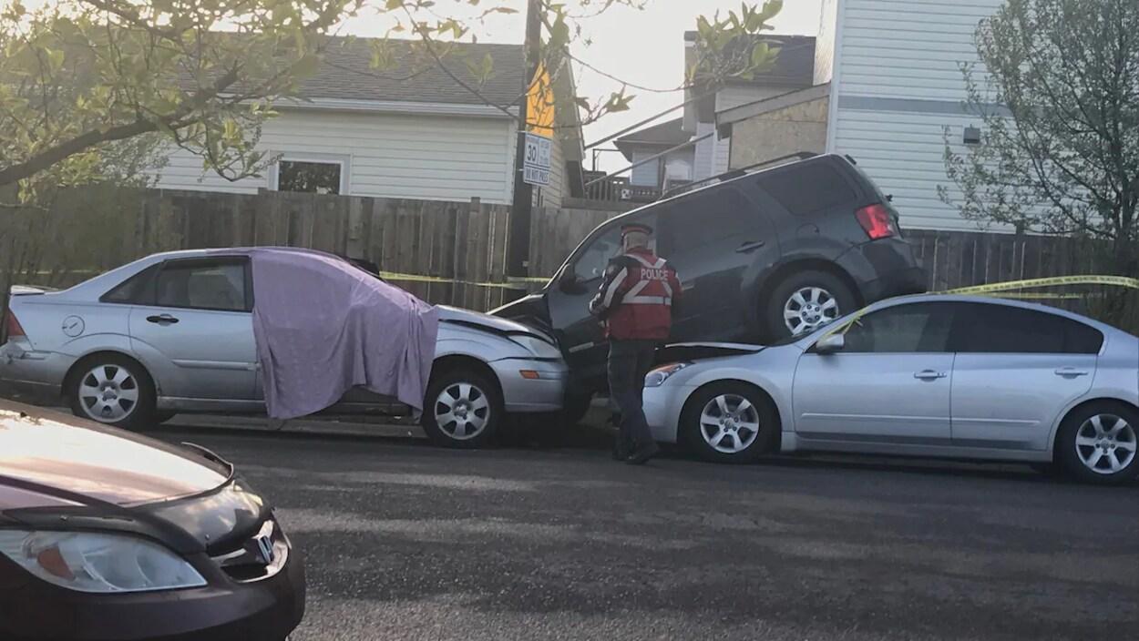 Une voiture noire est presque par dessus deux autres voitures sur le bord de la rue. Un policier l'examine.