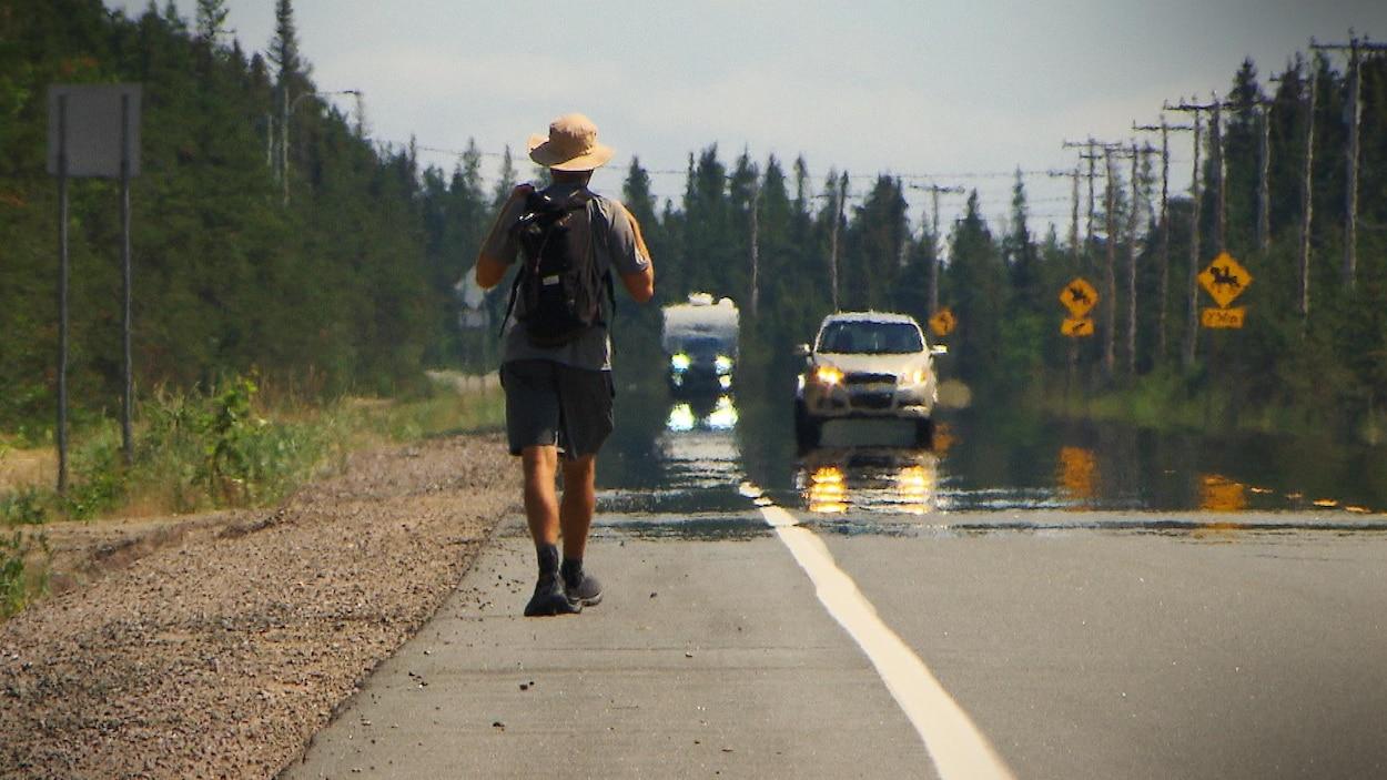 Un homme vu de derrière marche sur la route 138 face à des véhicules qui circulent vers lui.