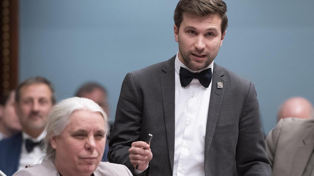 Gabriel Nadeau-Dubois debout à l'Assemblée nationale du Québec aux côtés de Manon Massé, assise.