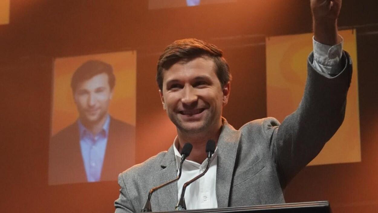 Gabriel Nadeau-Dubois sourit derrière un lutrin sur une scène éclairée en orange.