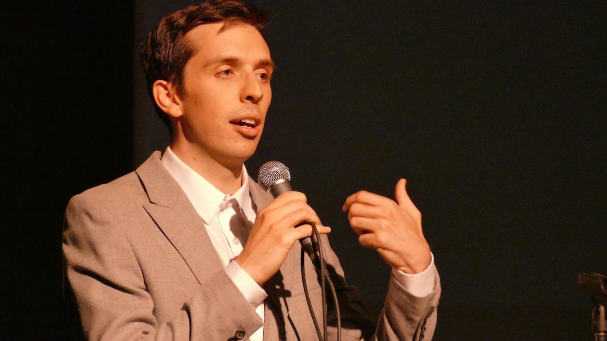 Un homme parle devant une foule.