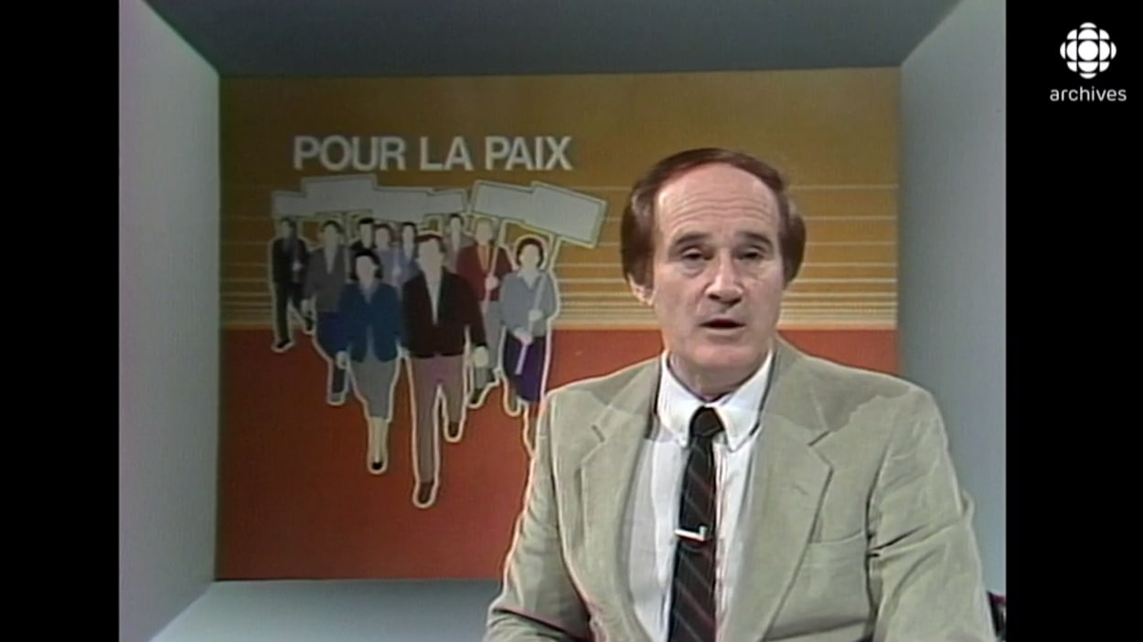 Le présentateur est devant une illustration de manifestants avec l'inscription « pour la paix ».
