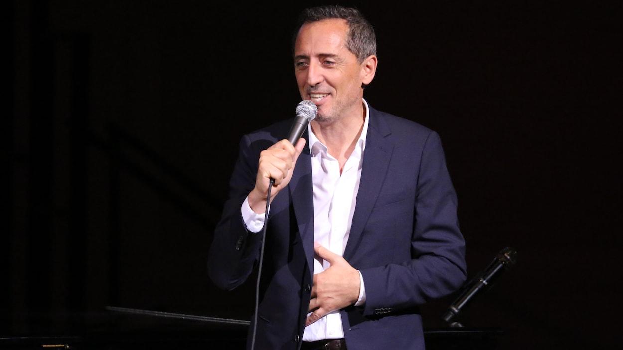 L'homme est sur une scène avec un micro et sourit.