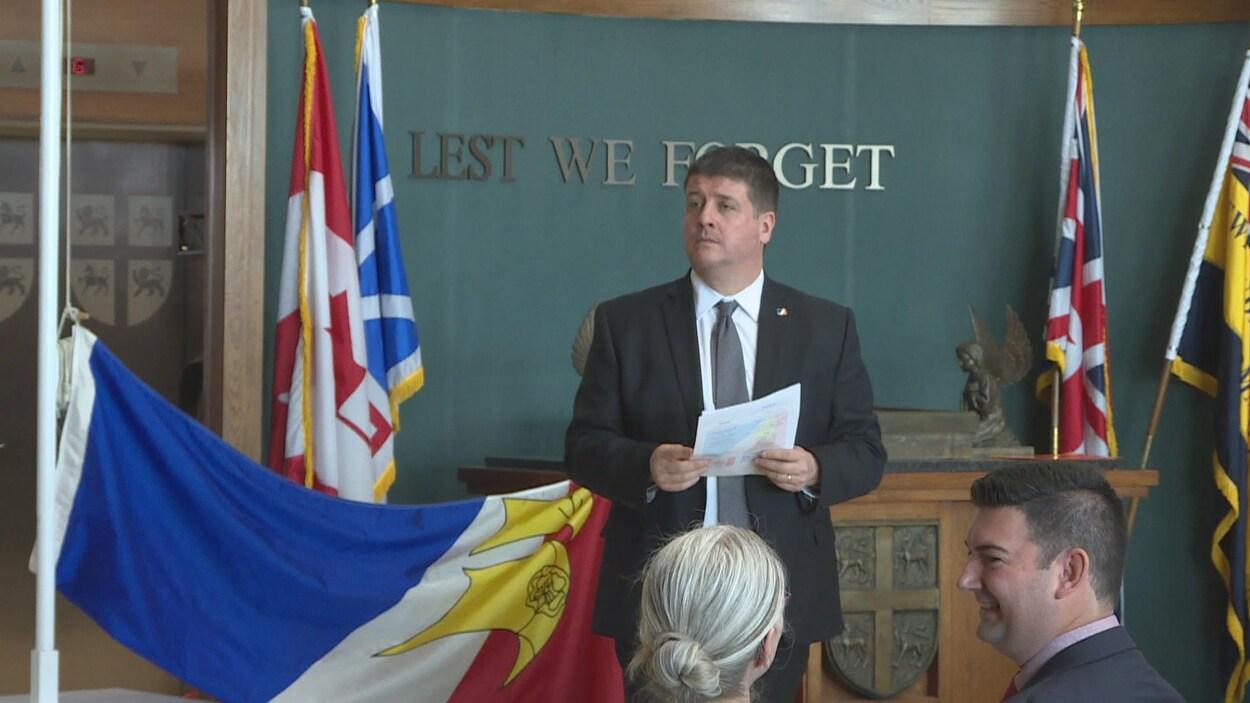 Gaël Corbineau est debout. À l'arrière plan, le drapeau de la francophonie.