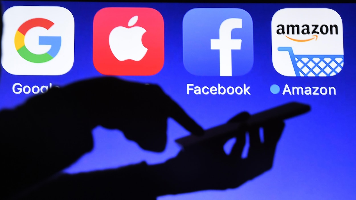 Une personne utilise un téléphone cellulaire devant un écran affichant des logos de Google, Apple, Facebook et Amazon.