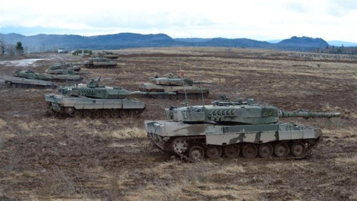 Une dizaine de chars d'assaut alignés dans un champ s'apprêtent à manoeuvrer