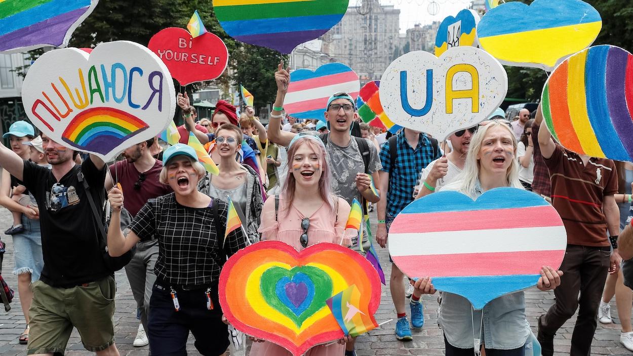 Des hommes et des femmes brandissent des pancartes en forme de cœurs multicolores dans une rue de Kiev, en Ukraine.