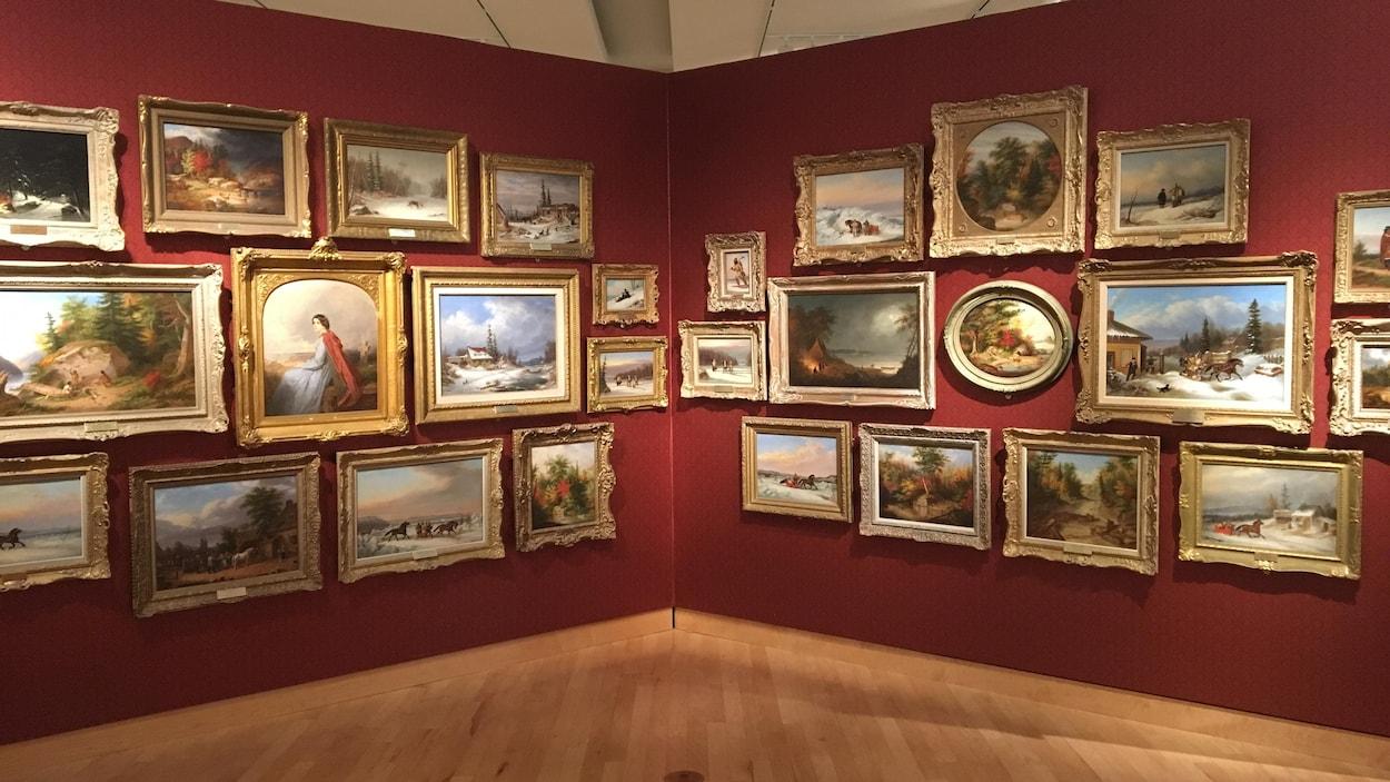 Deux murets sur lesquels sont accrochés des dizaines de tableaux de Cornelius Krieghoff.
