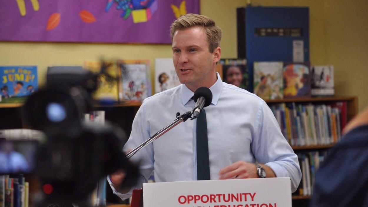 Brian Gallant donne une conférence de presse dans la section des livres pour enfants d'une bibliothèque publique.