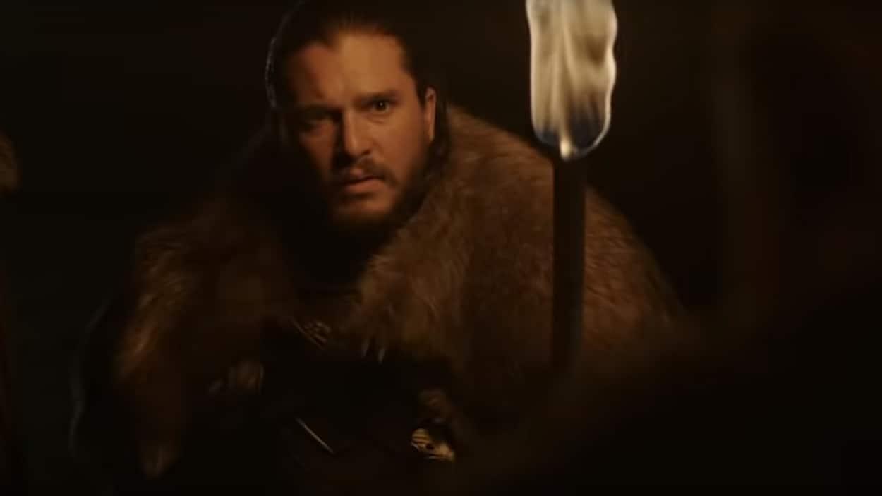 Jon Snow marche, le visage éclairé par un flambeau.