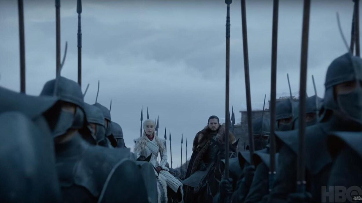 Daenerys et Jon Snow sont sur des chevaux, entourés de soldats à pied.