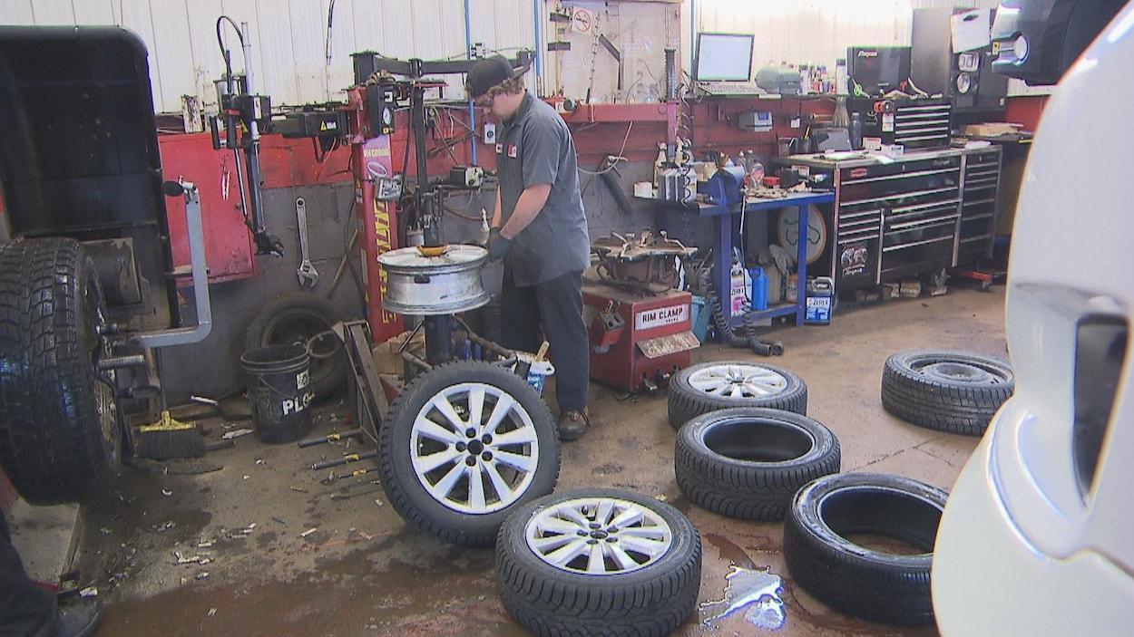 Un travailleur dans un garage avec des pneus.