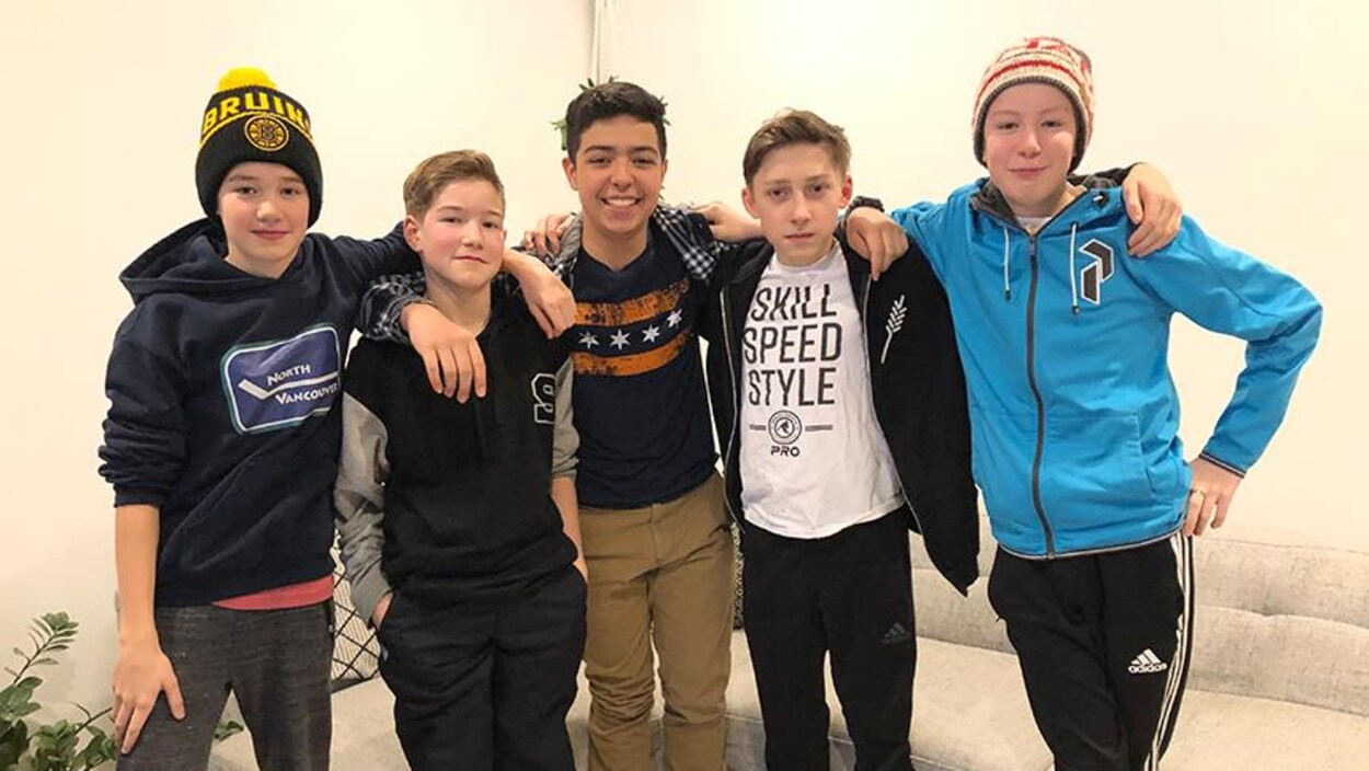 Cinq jeunes garçons sourient pour la caméra.