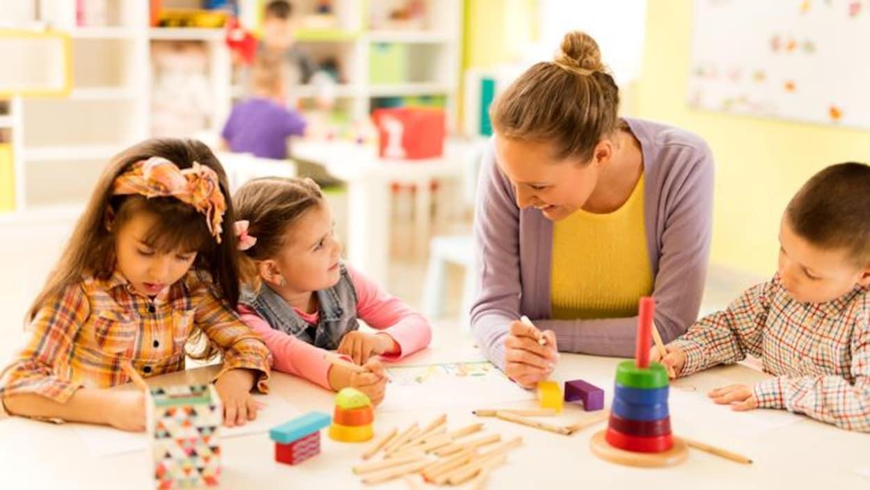 Une jeune femme dessine avec des enfants dans une salle de classe.