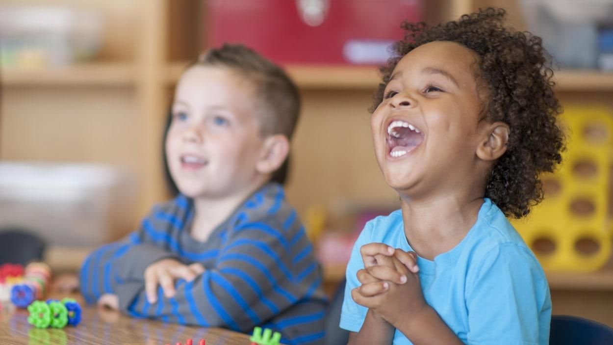Deux enfants sont assis à une table dans une garderie, dont un qui sourit à pleines dents.