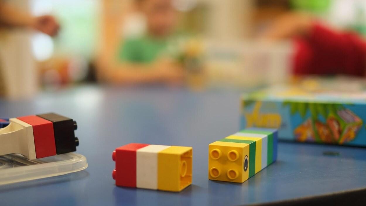 Gros plan sur des blocs déposés sur une table, avec des enfants en arrière-plan.