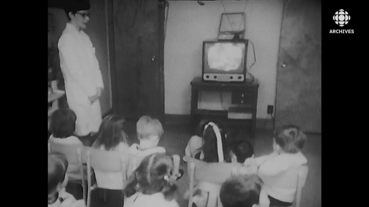 Un groupe d'enfants assis devant la télévision sous la supervision d'une éducatrice.