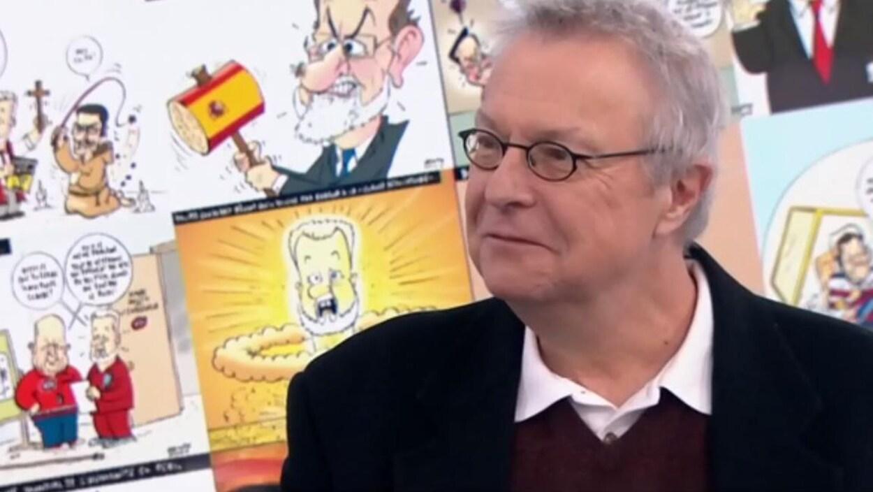 Michel Garneau souriant devant un écran où figure un collage de plusieurs de ses caricatures.