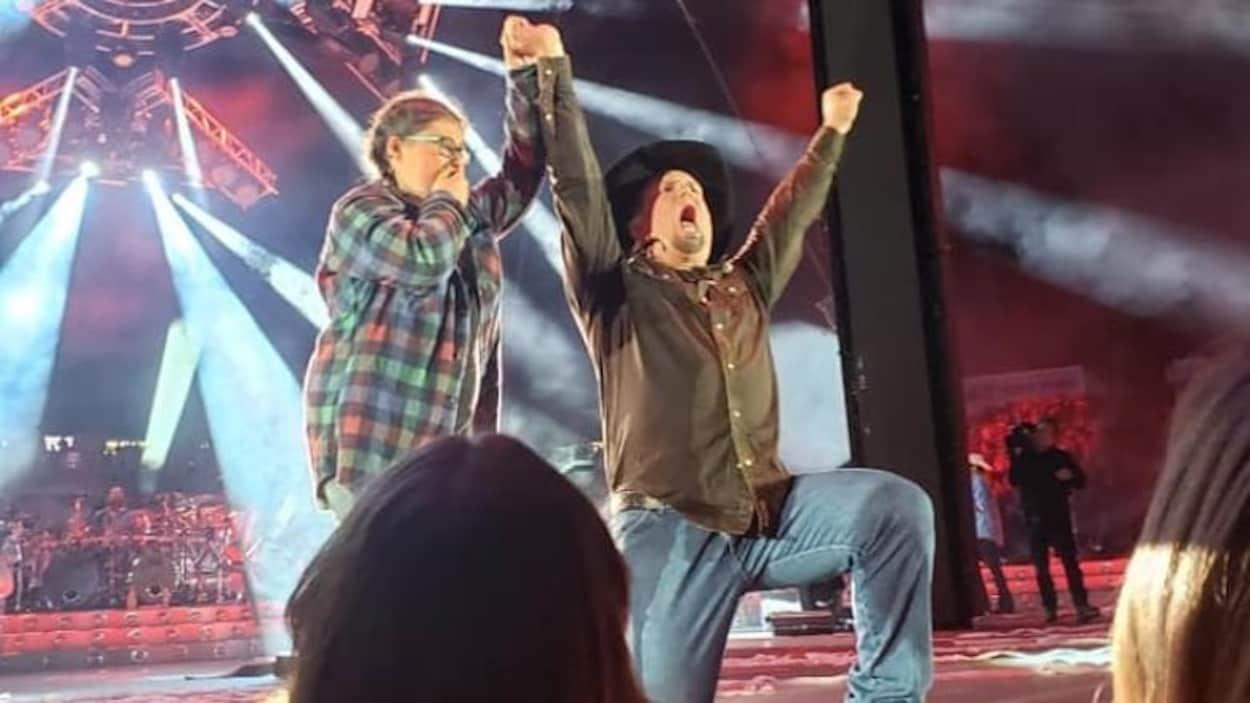 Garth Brooks agenouillé à côté de Camille Baragar sur la scène lève le bras de la jeune fille haut dans les airs.