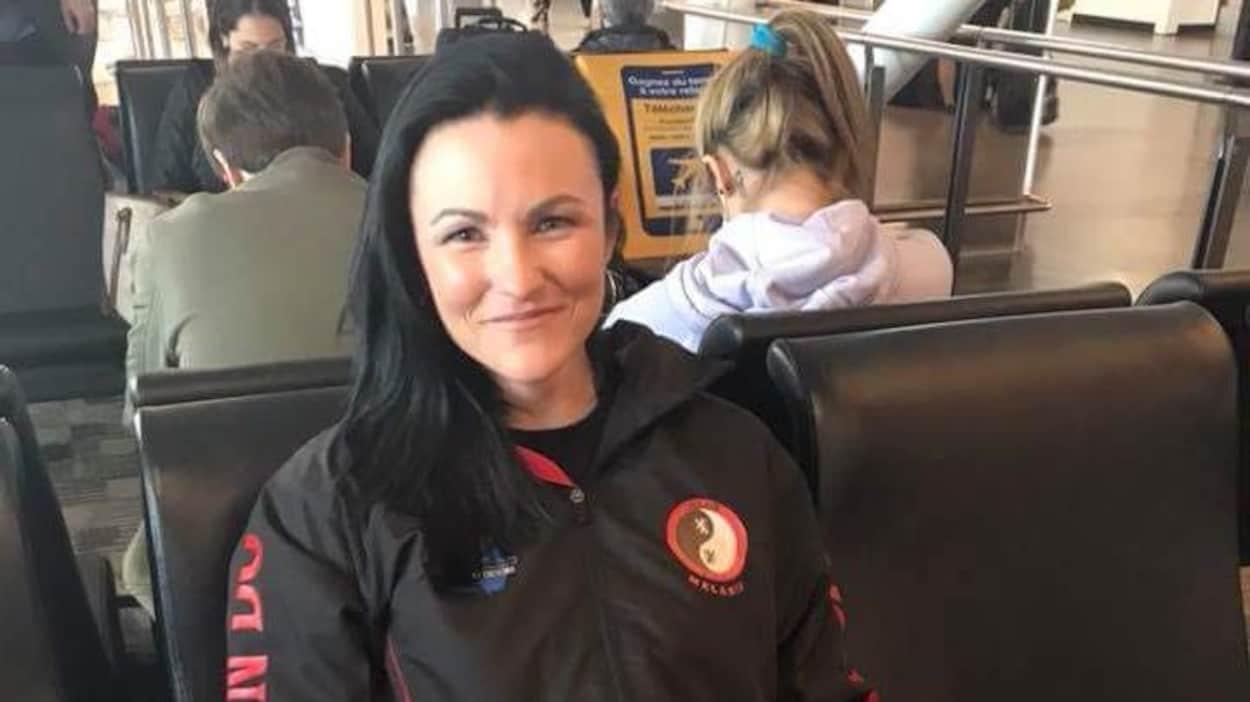 Une jeune femme assise dans une aire d'attente d'un aéroport.