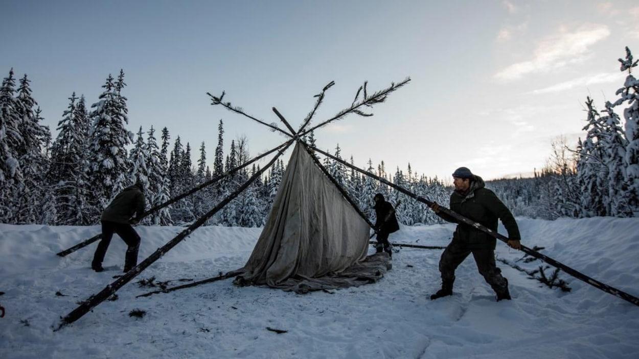 Des personnes montent une tente au milieu d'un chemin enneigé.