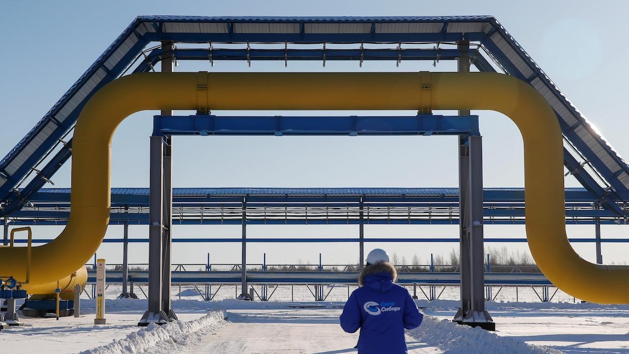 Un homme face à un gazoduc dans un lieu enneigé.
