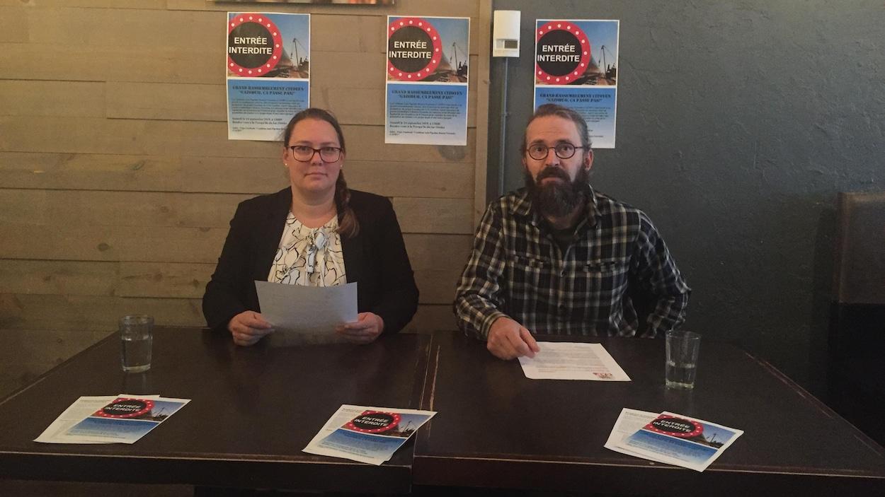 Marie-Ève Sigouin et Guillaume Marcotte sont assis devant une table où des pamphlets anti-gazoduc sont déposés.
