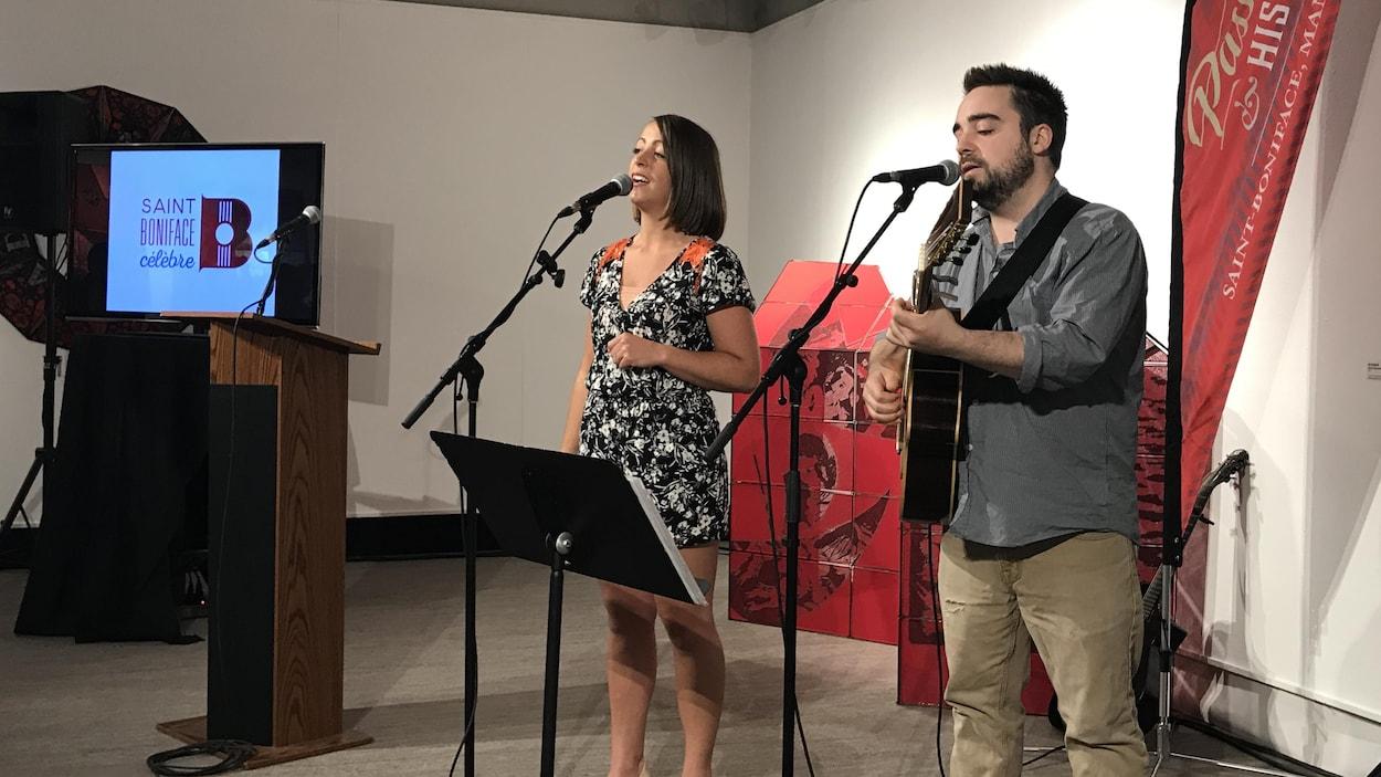 Une femme et un homme chantent au micro dans la galerie d'un musée. Au fond, un écran montre le logo de « Saint-Boniface célèbre ».