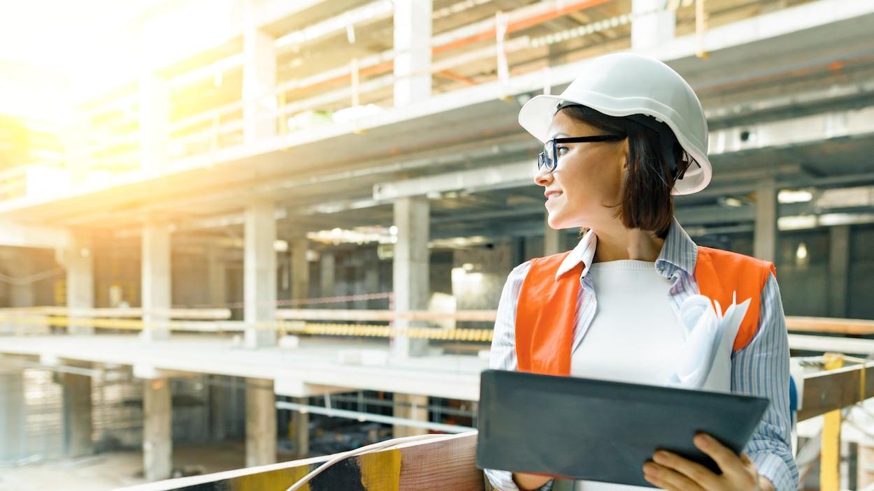 Une femme portant un casque protecteur et un gilet voyant se trouve sur un site en construction. Elle tient également une tablette dans ses mains et porte des lunettes.