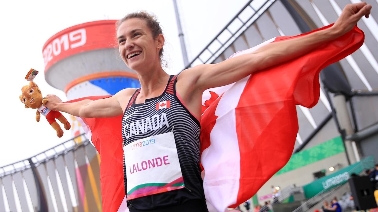 Geneviève Lalonde avec le drapeau du Canada et une peluche de la mascotte des Jeux panaméricains après sa victoire.