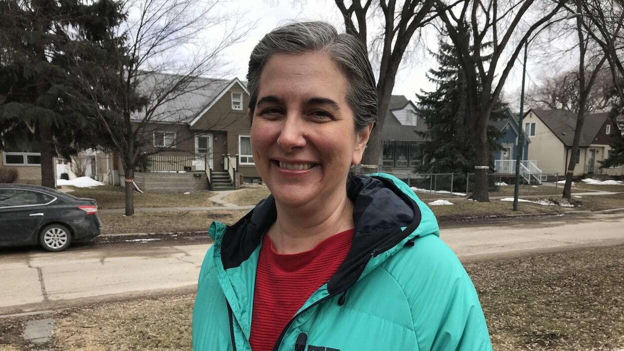 Une femme avec un manteau bleu-vert et un chandail rouge, sur le trottoir, dans un quartier résidentiel.