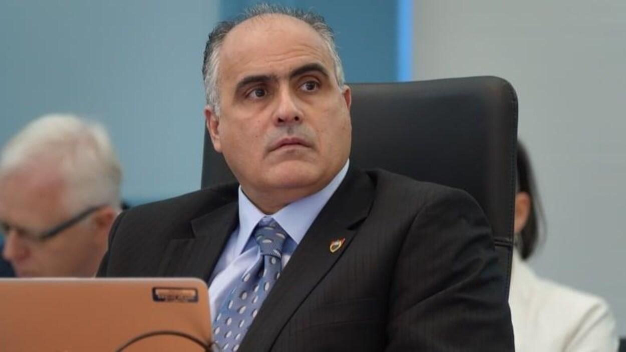 George Darouze assis dans une salle devant un ordinateur portable.
